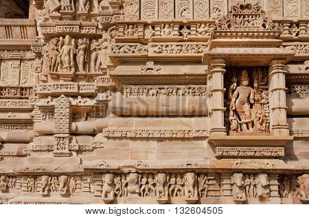 Brick wall with reliefs of Hindu temple of Khajuraho, India. UNESCO Heritage site built between 950 and 1150 in India belong to Hinduism and Jainism.