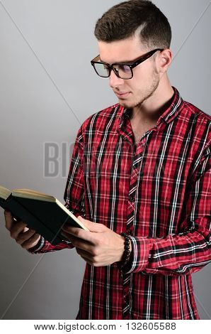 Young Student Wearing Glasses And Reading Book On Grey Background