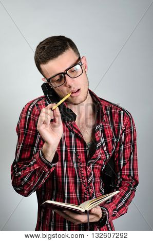 Young Man Talking By Telephone And Writing In Note