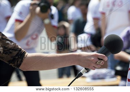 Media interview. Journalist holding a microphone conducting an TV or radio interview.