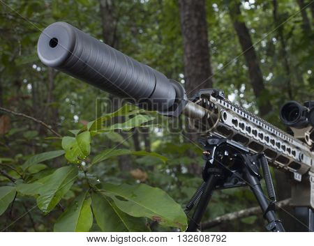 Silencer mounted on a modern sporting rifle in the trees