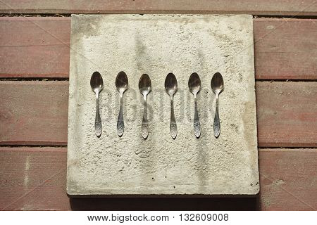 six little spoons on concrete and wood floor