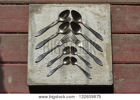 four big and little spoons and two forks on concrete and wood floor