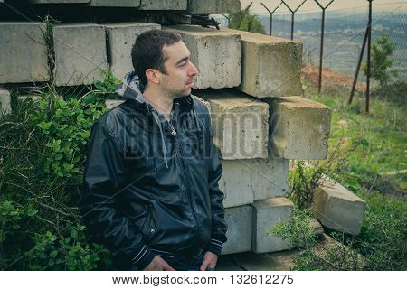 Man With Serious Face Posing Outdoor In Abandoned Industrial Place