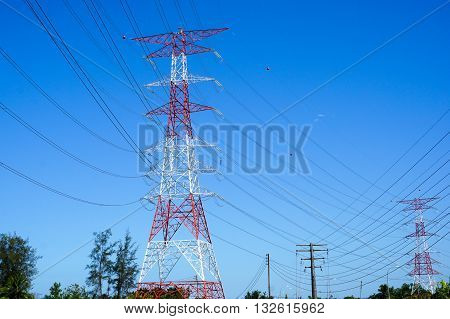 Electricity transmission pylon silhouetted against blue sky.