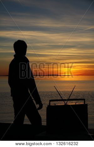 Man silhouette with a old radio in the sunset