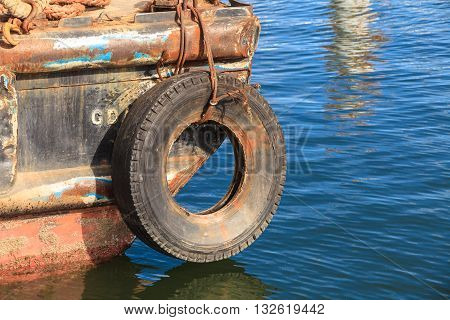 Old tire worn out hanging on lines. Daily work in rusty port. Workplace fishers.