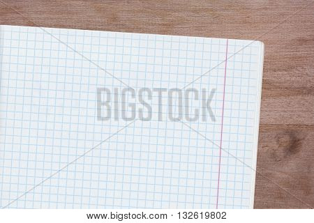 Sheet of paper from a notebook into a cell copyspace. Blank empty note pad on wood background. Notebook page.