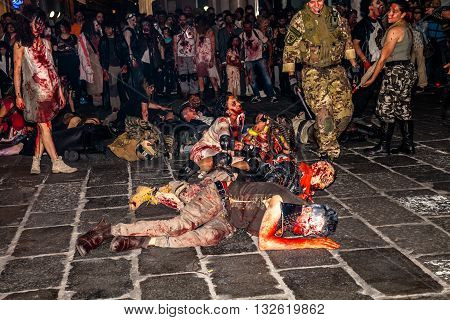 Bologna, Italy - May 21, 2016: Bologna zombie apocalypse walk: a group of zombies crawling on the ground.