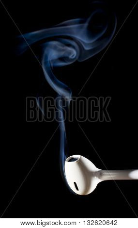 White ear bud on black that looks like it is about to burn out with smoke