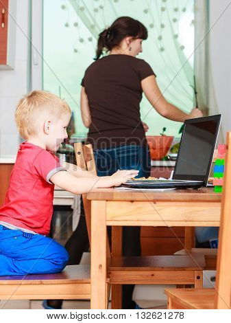 Technology and early education. Spending time with family. Child use laptop for fun and learning. Boy with computer and mother cleaning house.