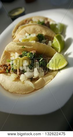 Three delicious carne asada tacos with lime and salsa