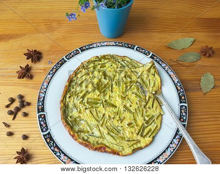 Greenery omelette with dandelions stalks and spices on plate