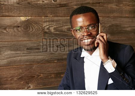 Successful African Entrepreneur In Formal Two-piece Suit Looking And Smiling At The Camera With Happ