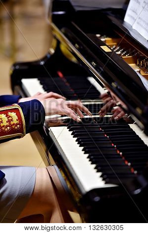 Hands of a woman part of a military orchestra performing at a piano during a concert