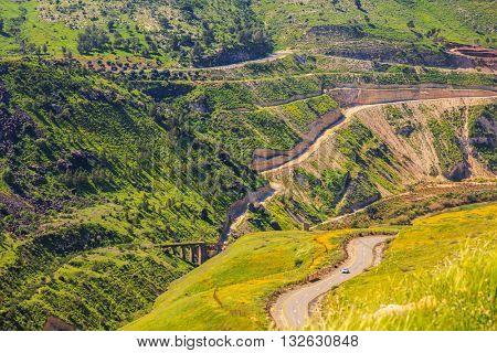Israeli-Jordanian border near the hot springs of Hamat Gader. Serpentine road winds through the green hills