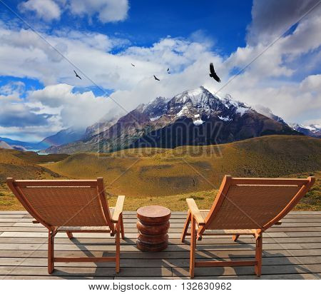 Pleasant holiday. Chile. Wooden chairs in the park Torres del Paine. On the horizon is visible snow-covered rocky mountain