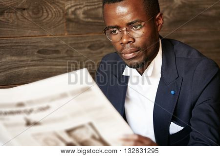 Close Up Portrait Of Serious Black Corporate Worker In Formal Two-piece Suit And Spectacles Holding