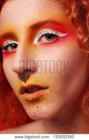 Beautiful Woman with Red Hair and bright makeup. High fashion look close up beauty portrait model with bright makeup with perfect clean skin . High key. nose piercing. creative make-up