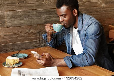 Young African Man Sitting At The Coffee Shop Sending Text Message From His Mobile Phone. Student Wea