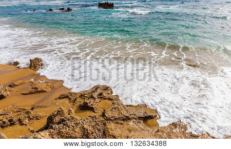 seascape with foamy waves swashing on the beach