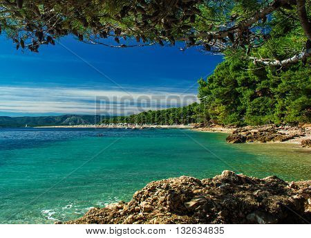beautiful view on zlatni rat beach with crystal clear turquoise water on island Brac Croatia in natural frame of pines and rocks