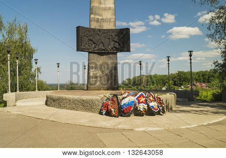 Monument and eternal flame with wreath on background blue sky
