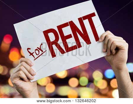 For Rent placard with night lights on background