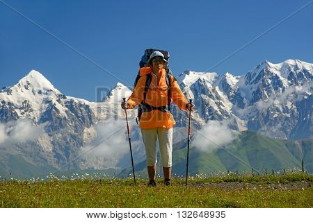 Tourist dressed in orange jacket against mountains covered with snow background. Alpine meadow in foreground.