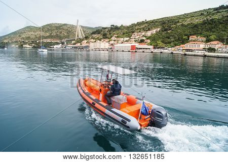 Tivat, Montenegro - 26 April, A man in a motorboat, 26 April, 2016. The town of Tivat and the coast of the Bay of Kotor in Montenegro.