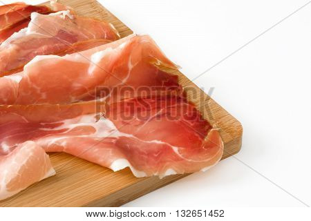 Thin slices of spanish serrano ham on a table isolated on white background