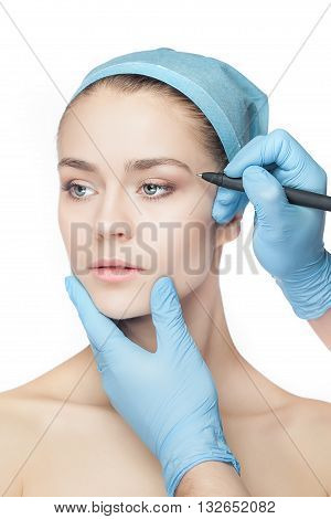 Beautiful young woman before plastic surgery operation. Beautician touching woman face.