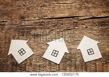 Three cardboard houses on the wooden background. wood construction