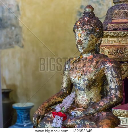 Buddha statue with sacred lei flower in Buddhist temple