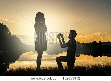 Marriage proposal concept. Man is kneeling and holds ring. Silhouettes in sunset.