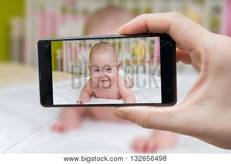 Parent is taking photo of a baby with smartphone.