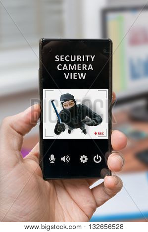 Security concept. Man holds smartphone with security camera view on thief or robber. Security alarm is recording burglar.
