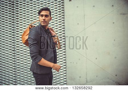 Stylish model looking man profile with handbag on his shoulder in modern architectural environment