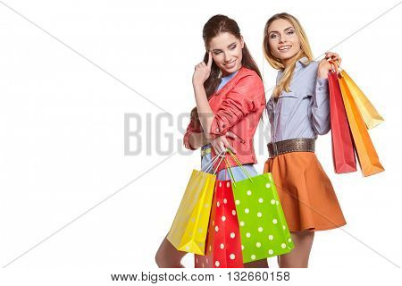 studio image of two beautiful young women, holding a few shopping bags, smiling and looking happy