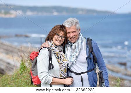 Smiling senior hiking couple standing by cliff