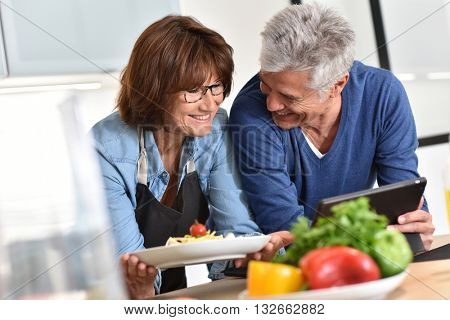 Senior couple in kitchen preparing dish together