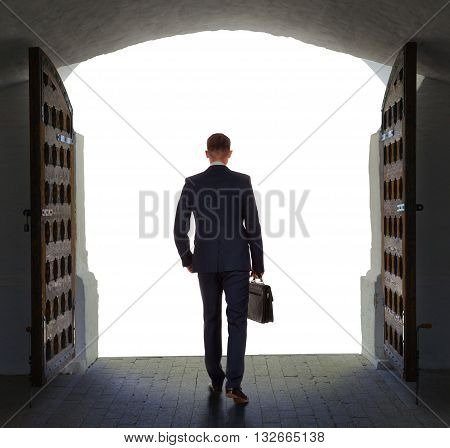 Young businessman finds exit and moves outside from old gate.