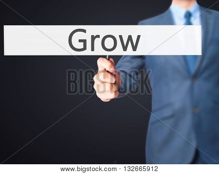 Grow - Businessman Hand Holding Sign