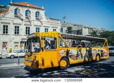 Dubrovnik Croatia - August 26 2015. People rides yellow tourist bus near the entrance to Old Town of Dubrovnik