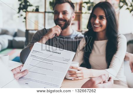 Discussing contract. Happy young couple sitting together at the desk and looking at man sitting in front of them and holding contract
