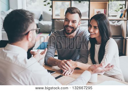 Thankful couple. Happy young loving couple bonding to each other and looking at man sitting in front of them at the desk and gesturing