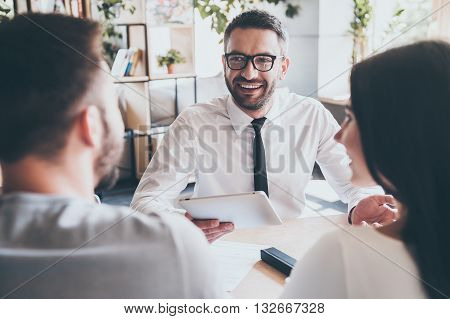 Great news for you! Cheerful mature man in shirt and tie holding digital tablet and gesturing while young couple sitting in front of him at the desk