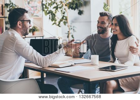 Good news! Happy young couple bonding to each other and listening to man sitting at the desk in front of them and gesturing
