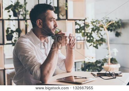 Waiting for inspiration. Side view of thoughtful young man holding cup of coffee and looking away while sitting in cafe