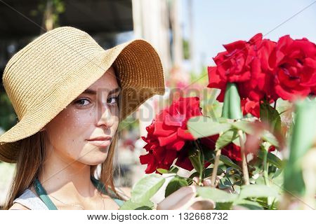 Young Flower Seller Takes Care Of Her Red Roses